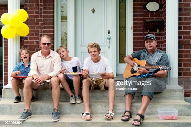 """three generation of males sitting on home porch. - """"martine doucet"""" or martinedoucet stock pictures, royalty-free photos & images"""