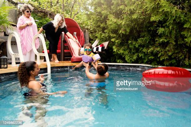 """three generation of mixed-race family having fun in the pool. - """"martine doucet"""" or martinedoucet stock pictures, royalty-free photos & images"""