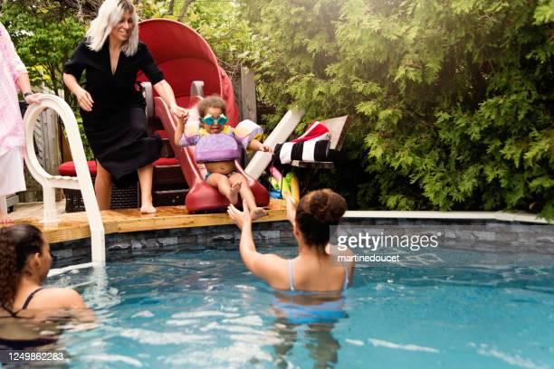 """tre generationer av blandad ras familj ha kul i poolen. - """"martine doucet"""" or martinedoucet bildbanksfoton och bilder"""