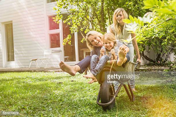 Three generation of women having fun with wheelbarrow