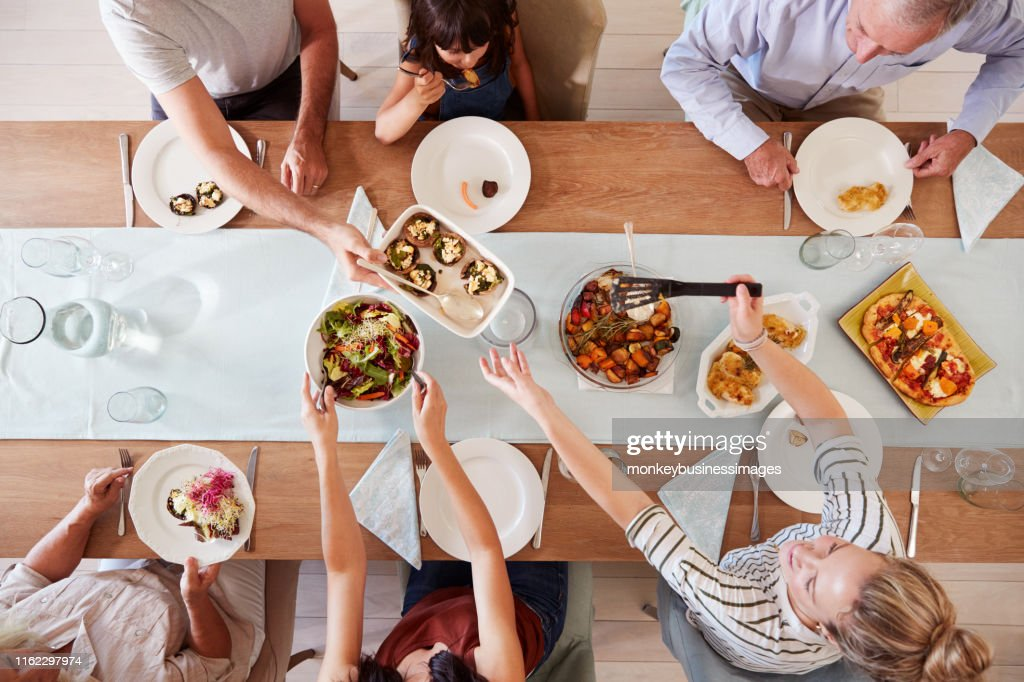 Three generation white family sitting at a dinner table together serving a meal, overhead view : Stock Photo