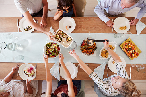 Three generation white family sitting at a dinner table together serving a meal, overhead view 1162297974