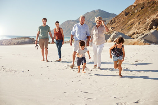Three generation white family walking together on a sunny beach, kids running ahead 1162303350