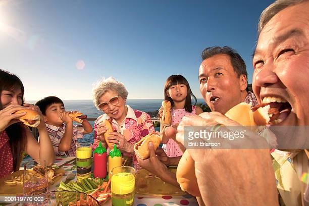 Three generational family eating hotdogs outdoors