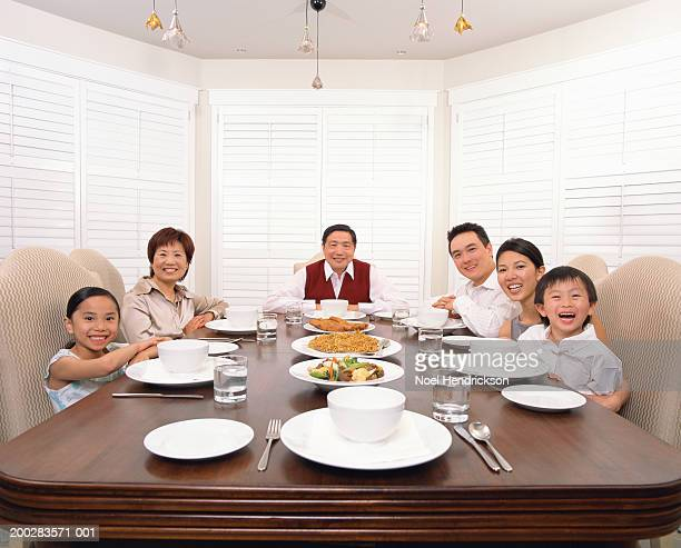 Three generational family gathered around dinner table, portrait