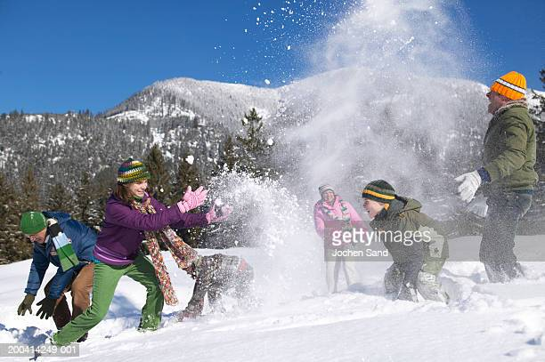 three generational family having snow ball fight, in alpine landscape - girl fight stock photos and pictures