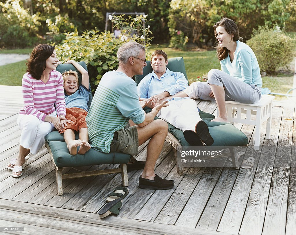 Three Generational Family Sit on Decking in Their Garden : Stock Photo