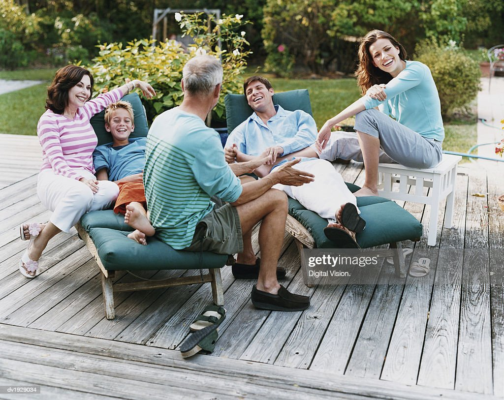 Three Generational Family Sit on Decking in Their Garden, Talking and Laughing : Stock Photo