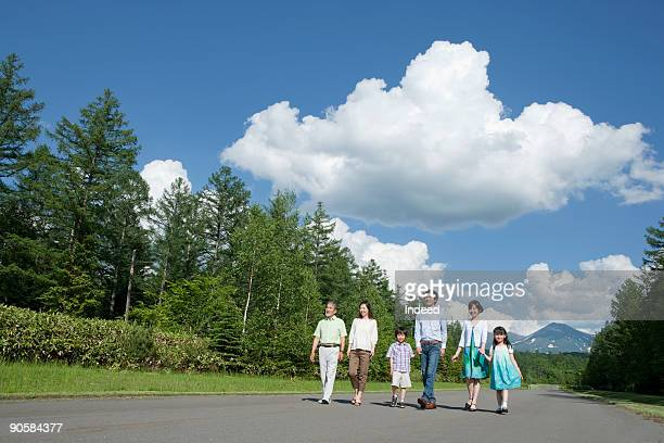 Three generational family walking on road