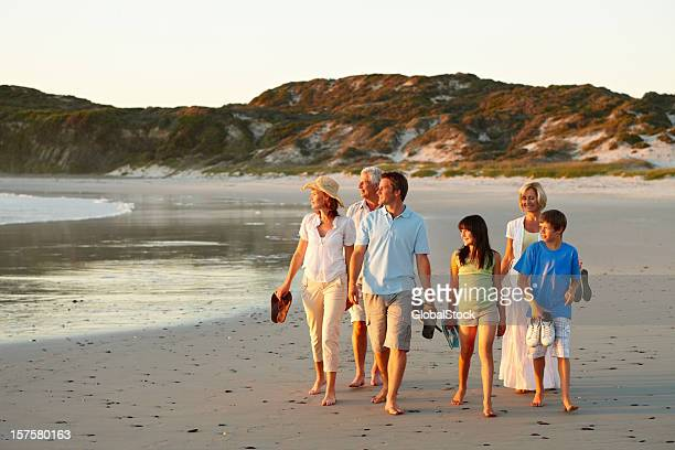 Three generational family walking together on beach