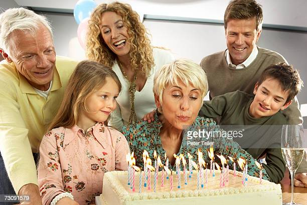 Three generational family with children (5-10 years), grandmother blowing out candles on birthday cake