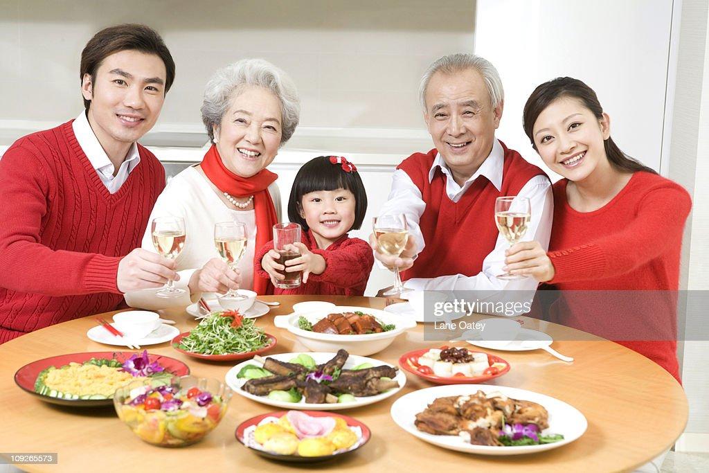 three generations enjoying a chinese new year dinner together stock photo - Chinese New Year Dinner