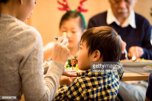 3 世代家族のクリスマス ディナーを楽しんで - ダイニングテーブル ストックフォトと画像