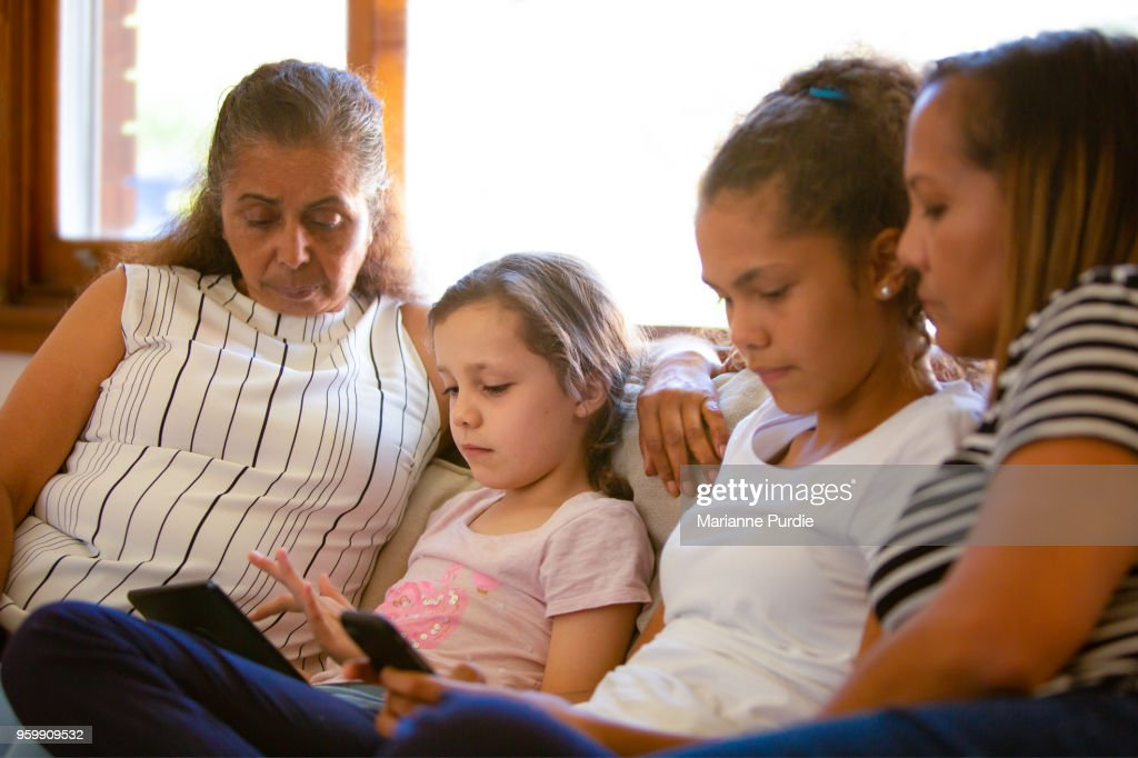 Three generations, grandmother, mother and daughters sharing technology in the lounge : Stock-Foto