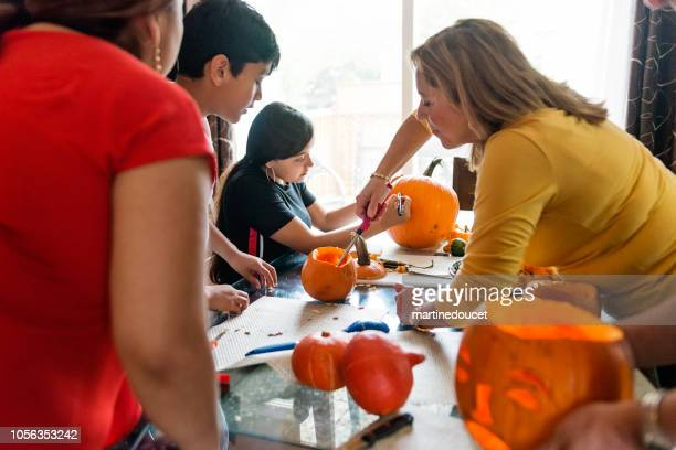 Three generations Latin American family carving pumpkins for Halloween