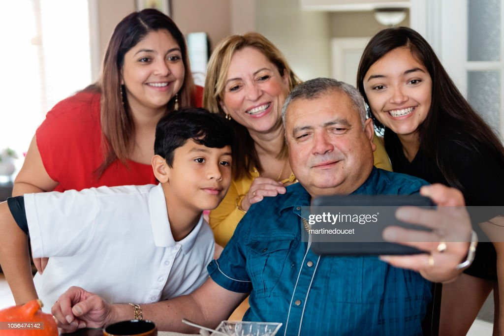 Three generations Latin American family taking selfie at meal time. : Stock Photo