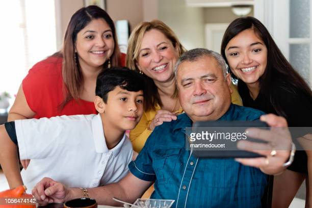 Three generations Latin American family taking selfie at meal time.