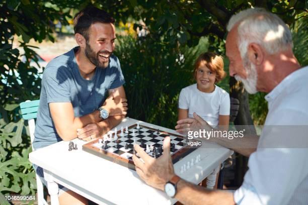 drei generationen männer spielen schach zusammen - schach stock-fotos und bilder