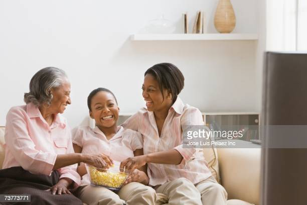 Three generations of African women eating popcorn on sofa