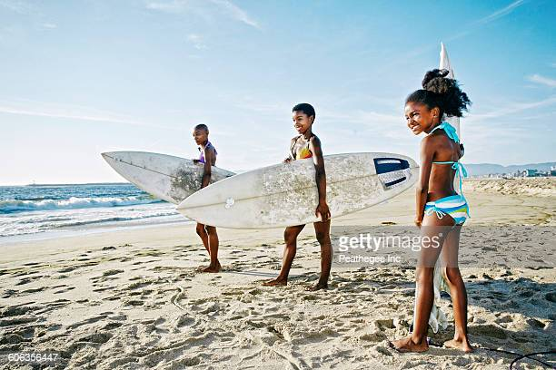 Three generations of Black women carrying surfboards on beach