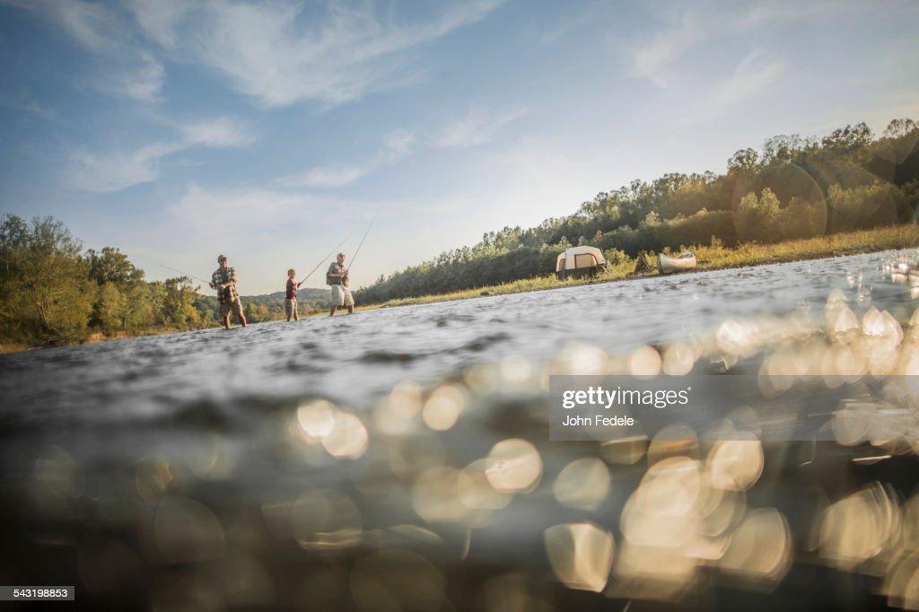 Three generations of Caucasian men fishing in river : ストックフォト