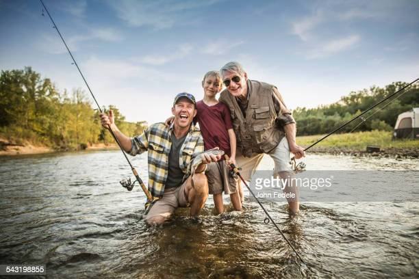 Three generations of Caucasian men fishing in river
