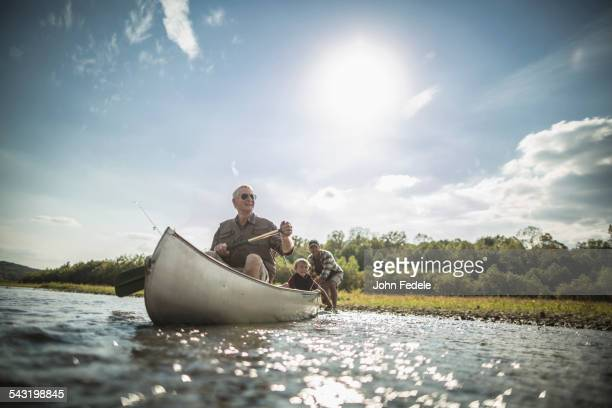 Three generations of Caucasian men paddling canoe in river