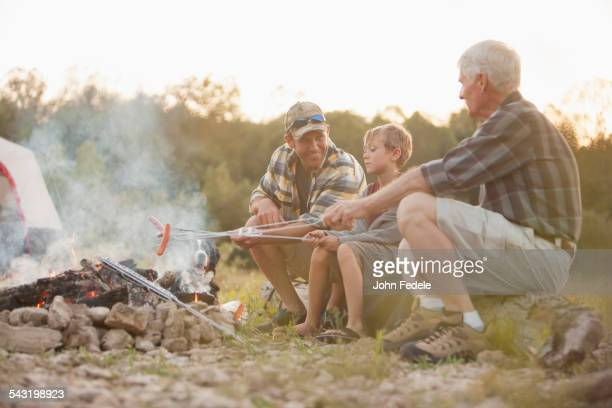 Three generations of Caucasian men roasting hot dogs over campfire