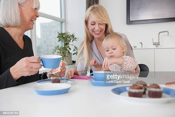 Three generations of Caucasian women eating cupcakes