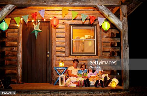 Three generations of Caucasian women reading on cabin porch