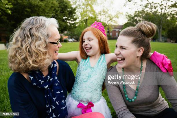 Three generations of Caucasian women sitting in park
