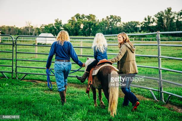 Three generations of Caucasian women walking miniature horse on farm