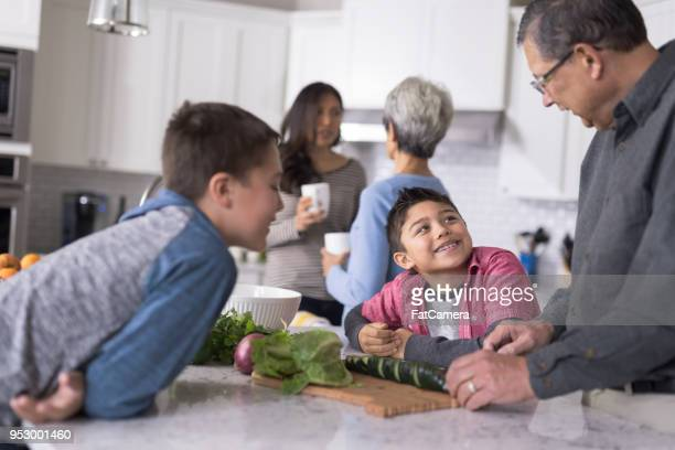 Three generations of family making lunch together in a modern kitchen