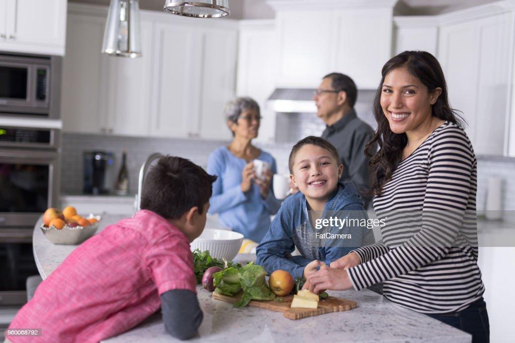 Drei Generationen der Familie Mittagessen gemeinsam in einer modernen Küche zu machen : Stock-Foto