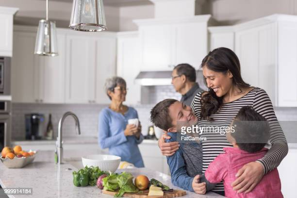 three generations of family making lunch together in a modern kitchen - pacific islander ethnicity stock pictures, royalty-free photos & images