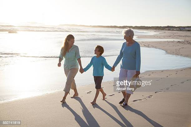 three generations of family on beach - white trousers stock pictures, royalty-free photos & images