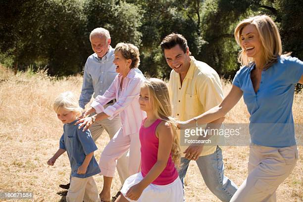 three generations of family walking in park - medium group of people stock pictures, royalty-free photos & images