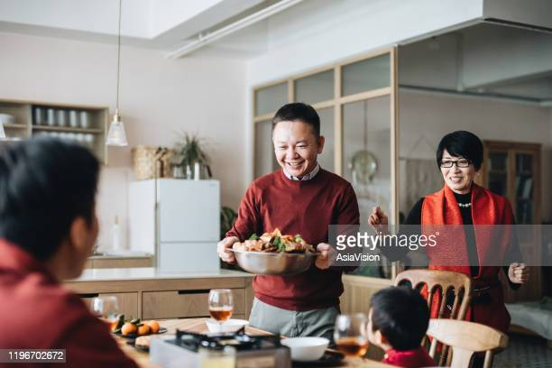 three generations of joyful asian family celebrating chinese new year and grandparents serving traditional chinese poon choi on reunion dinner - prosperity stock pictures, royalty-free photos & images