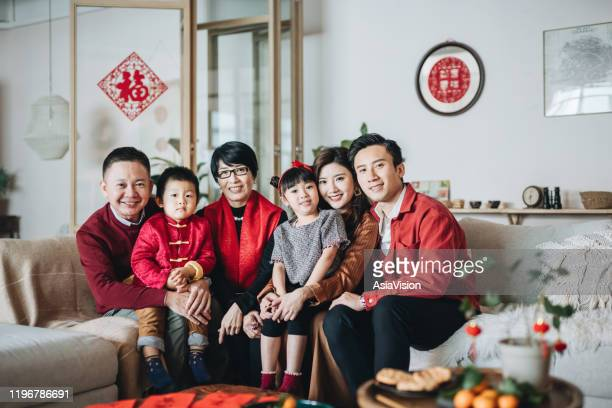 three generations of joyful asian family embracing and celebrating chinese new year together - chinese ethnicity stock pictures, royalty-free photos & images