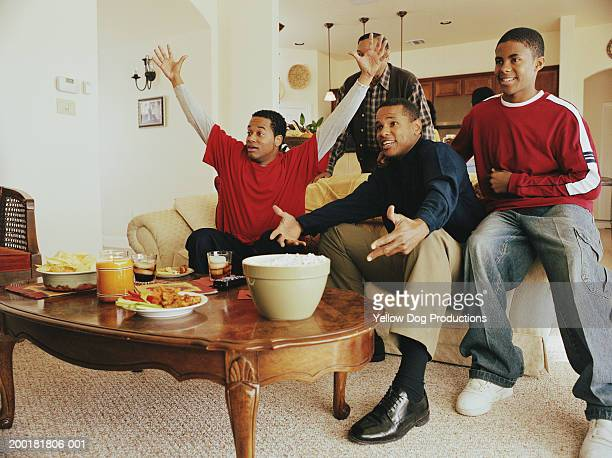 Three generations of men cheering in living room