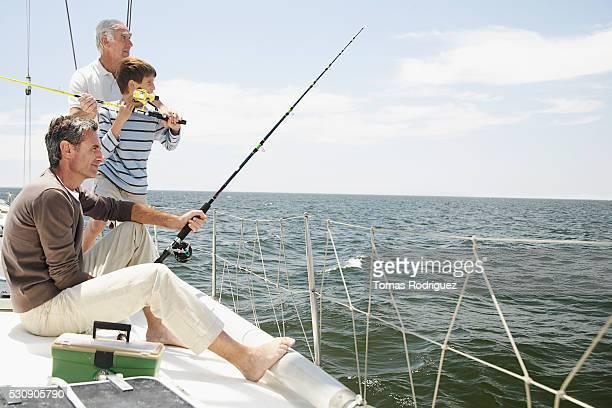 Three generations of men fishing off of boat