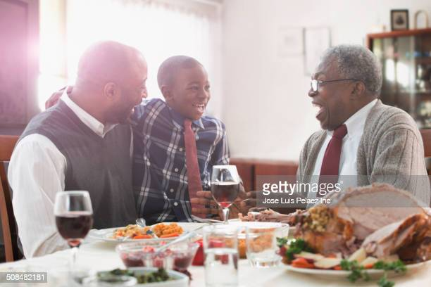 three generations of men talking at holiday table - funny turkey images stock photos and pictures