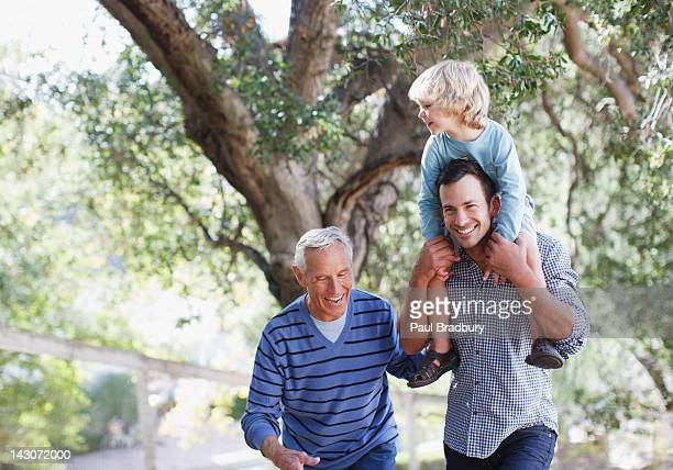three generations of men walking outdoors - multi generation family stock pictures, royalty-free photos & images