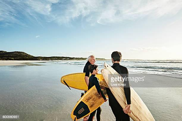 three generations of surfers on beach - senior adult stock-fotos und bilder