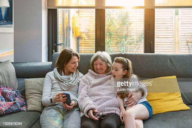 three generations of the same family laughing at something funny on the smartphone - single mother stock pictures, royalty-free photos & images