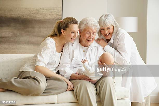three generations of women admiring baby - generation gap stock pictures, royalty-free photos & images