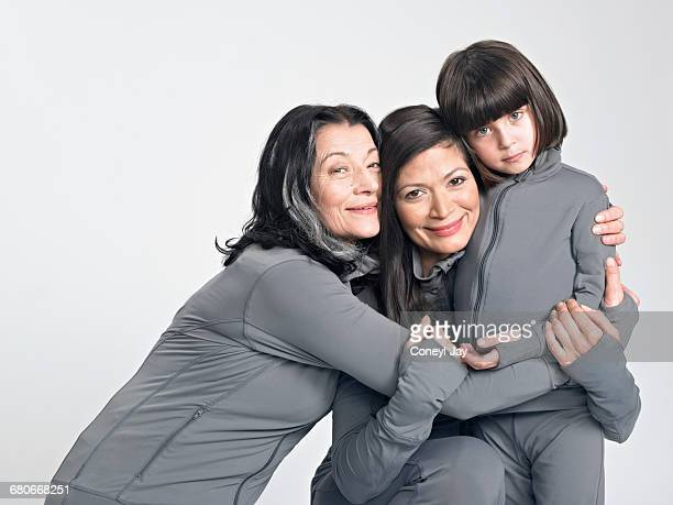 Three generations of women hugging.