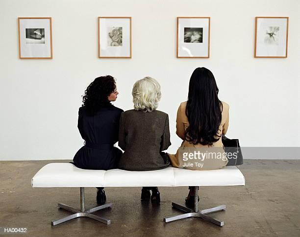 Three generations of women looking at exhibit in art gallery