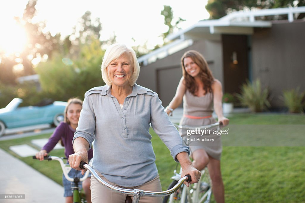 Three generations of women riding bicycles : Stock Photo