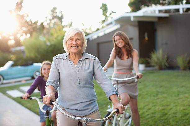 three generations of women riding bicycles - grandmother mother daughter stock pictures, royalty-free photos & images